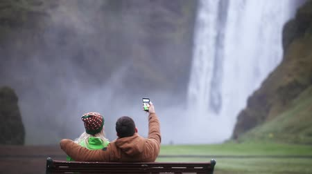 skogafoss : Back view of young couple sitting on the bench and taking selfie photo on smartphone. Skogafoss waterfall in Iceland. Stock Footage