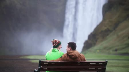 skogafoss : Back view of young tourists couple resting near the waterfall Skogafoss in Iceland. Man and woman on the bench.
