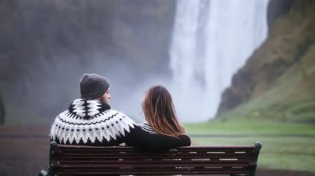 romance : Back view of young couple sitting on the bench and resting. Beautiful landscape of the Skogafoss waterfall in Iceland.
