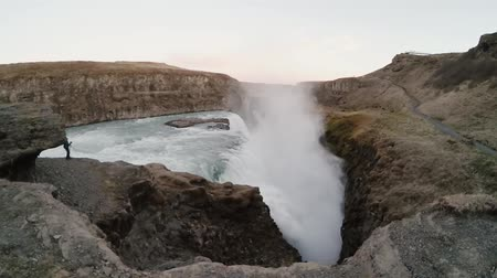 gullfoss : Young tourist man taking photos of beautiful Gullfoss waterfall in Iceland. Traveling male exploring the new place. Stock Footage