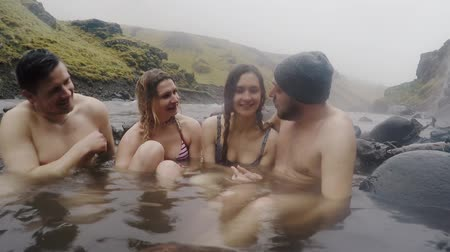 molas : Hot spring geothermal spa on Iceland. Two traveling couple relaxing in hot pool on Iceland. Tourists enjoying bathing.