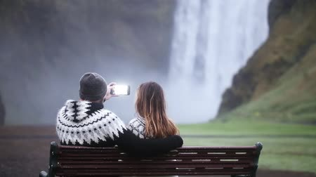 skogafoss : Young couple taking the photo on smartphone of the beautiful waterfall Skogafoss in Iceland, famous tourist place.