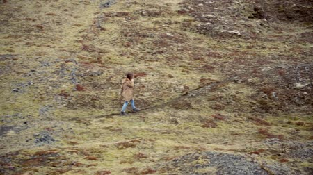 endure : Young traveling woman walking in mountain valley alone in windy day. Female exploring new place and thinking.