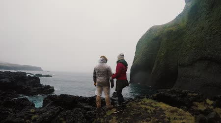 raincoat : Back view of young traveling couple standing on the rocks near the sea and enjoying the beautiful view together.