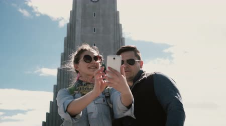 lutheran : Young happy couple taking the selfie photo on smartphone near the Hallgrimskirkja church in Reykjavik, Iceland. Stock Footage