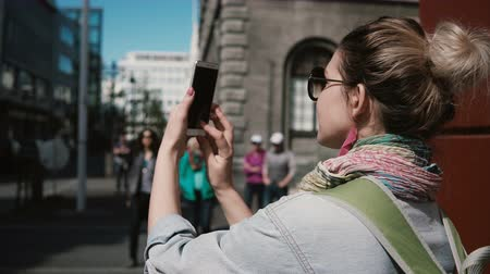 reykjavik : Young stylish woman standing on street and taking photo of the buildings. Female uses the smartphone for photographing. Stock Footage