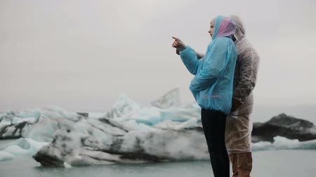 glacier point : Young traveling couple wearing raincoats enjoying the view in ice lagoon in Iceland. Tourists on the nature at cold day.