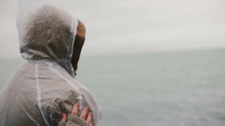 iceberg : Happy young traveling couple in raincoats in Iceland looking on something interesting. Man and woman points with finger. Stock Footage