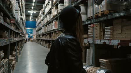 ремонт : Young beautiful woman walking through the high shelves with goods in big building store and choosing the things to buy.