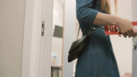 liquidação : Close-up view of young woman walks through the corridor and puts on knob the door hanger, asking do not disturb her.