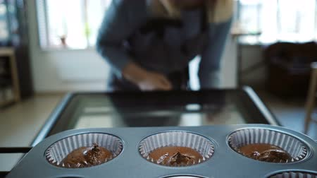 housekeeper : Young woman opens the oven and gets out the baking tray for cupcakes. Attractive female cooking desserts. View inside.