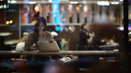 müdür : View inside the window on beautiful woman using the laptop in evening. Female closing the computer and leaving the cafe.