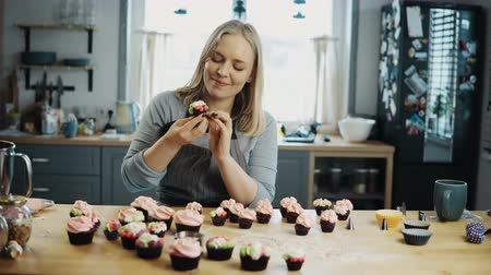 сладости : Young woman standing on the kitchen and tasting chocolate cupcakes with cream on the top. Confectioner prepares muffins.