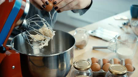 baking dishes : Close-up view of young female hands mixing the ingredients in big bowl with mixer. Female cooking on the kitchen. Stock Footage