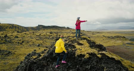 bumps : Aerial view of the group of tourists hiking on lava field in Iceland. Two woman raise hands up, feel happy and freedom. Stock Footage
