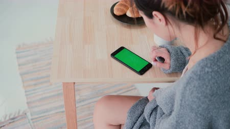 sharing : Young woman sitting at the table and touching the screen in kitchen. Girl uses smartphone, green screen during breakfast