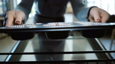 housekeeper : View inside the oven. Young woman open the oven and puts on the baking dish with dough, cooking the cupcakes.