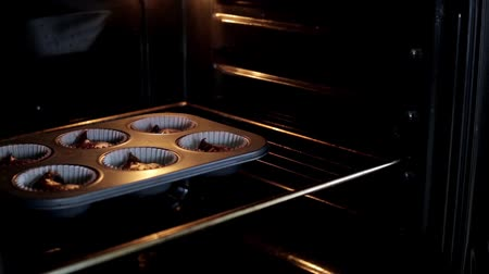 muffin : Young woman open the oven and puts on the baking dish with dough. Female cooking the cupcakes in the kitchen. Stock Footage