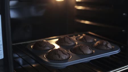 queque : Close-up view of young woman opens the oven and gets out the baking tray for cupcakes. Female cooking the desserts.