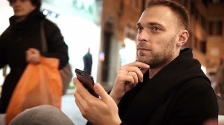 internet things : Young handsome man with beard sitting in the cafe and spending leisure time in city centre and using the smartphone. Stock Footage