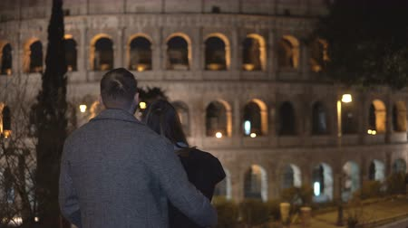 dátum : Back view of young man and woman standing near the Colosseum in Rome, Italy and hugging together.