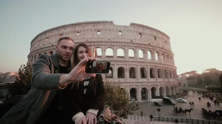 dinlenmek : Young happy couple taking a selfie photo on smartphone. Attractive man and woman near the Colosseum in Rome, Italy. Stok Video