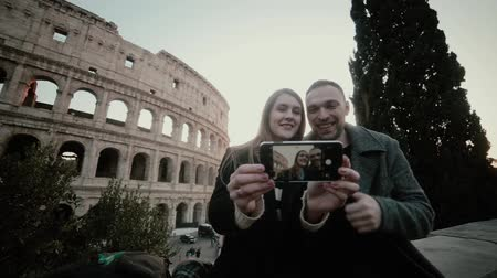 dinlenmek : Young beautiful couple sitting near the Colosseum in Rome, Italy and taking selfie photo on smartphone together. Stok Video