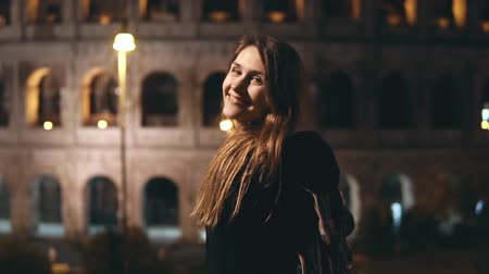 Колизей : Young beautiful woman standing near the Colosseum in Rome, Italy, looks back in camera and smiling in the evening.