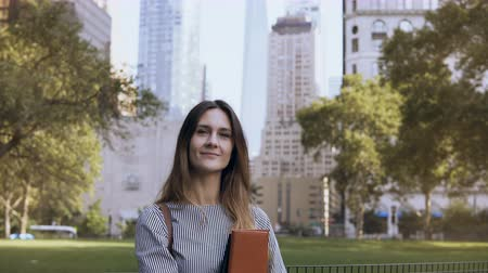 notebooks : Portrait of young smiling woman in New York, USA. Beautiful businesswoman holding the documents and looking at camera. Stock Footage
