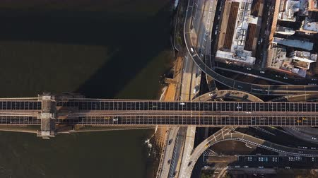 megalopolis : Aerial top view of Brooklyn bridge through the East river and road junction on Manhattan side in New York, America.