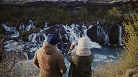 на камеру : Back view of young traveling couple standing in mountains near the waterfalls in Iceland and taking photo on smartphone