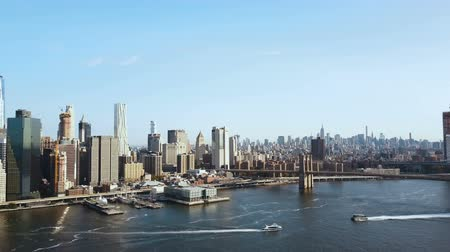 лодки : Aerial view of the Brooklyn bridge through the East river to Manhattan in New York, America. Boat riding on the shore.