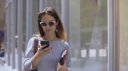 megalopolis : Young beautiful businesswoman in sunglasses holding documents and using smartphone, walking in the street. Slow motion. Stock Footage