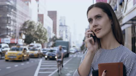 communion : Young businesswoman working on the street in New York, America. Female manager talking on smartphone in downtown.
