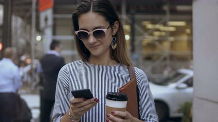 megalopolis : Portrait of young beautiful businesswoman with coffee cup and documents on crowded street using the smartphone.