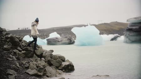 meditativo : Young attractive woman in lopapeysa standing in ice lagoon. Tourist exploring the famous sight of Iceland alone.
