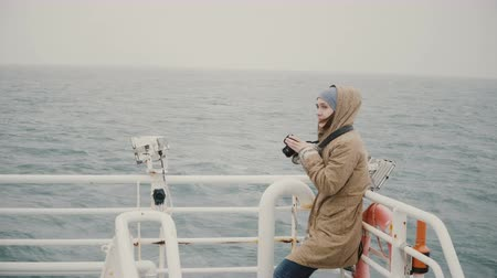 ferryboat : Young female journalist standing on the board of the boat and taking photos on the camera in overcast day.