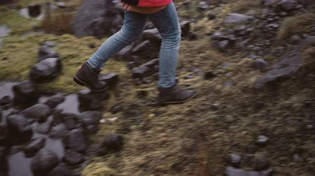 bumps : Back view of young woman hiking in rocky hills. Traveling female exploring the Iceland alone, walking through the bogs.