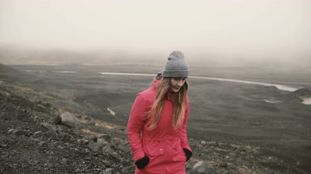 willpower : Young attractive woman walking in volcanic black mountains alone. Tourist exploring the Iceland, going to ice lagoon. Stock Footage
