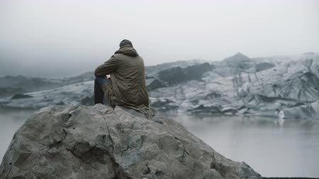mavi arka : Back view of young tourist sitting on the rock and looking on the glaciers in ice lagoon. Man exploring Iceland alone. Stok Video