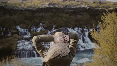 north stream : Back view of young traveling woman standing in mountains valley and looking on waterfalls in Iceland alone.