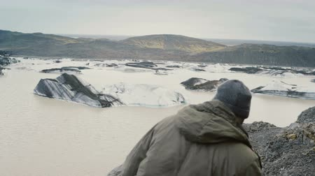 izlenim : Young handsome man hiking in the mountains near the Vatnajokull ice lagoon, looking on glaciers in Iceland.