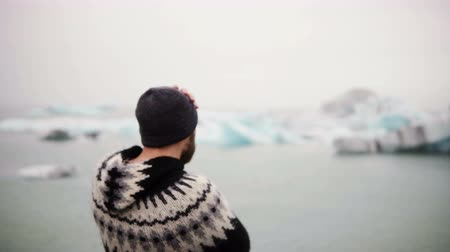 expedição : Young bearded man standing in Jokulsalon ice lagoon and looking on glaciers, North nature in Iceland.
