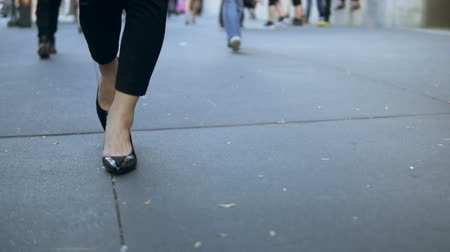 zebras : Close-up view of young female walking through the downtown. Businesswoman wearing black shoes with heels. Slow motion.