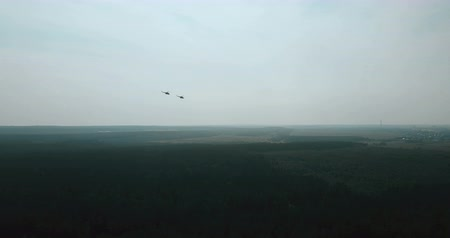 two forces : Aerial view of two helicopters flying close. Military aircraft flying in formation over green forest to city far away. Stock Footage