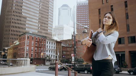 punctuality : Young beautiful businesswoman walking in financial district in New York, America, looking on watch. Slow motion. Stock Footage