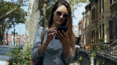 internet things : Portrait of young beautiful woman in sunglasses walking outside in sunny summer day and using smartphone. Slow motion. Stock Footage