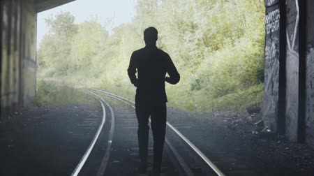 pursue : Slow motion man silhouette running on train tracks. Back view. Abstract background ending shot. In pursuit for freedom. Stock Footage