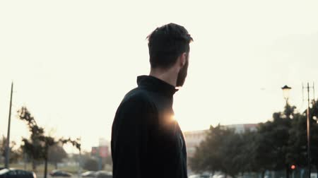 pináculo : Incredible cinematic shot of man looking back. Back view slow motion. Amazing sun glare. Reflecting and thinking.