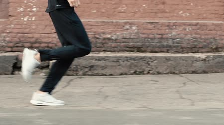 выстрел : Side view of man running fast along old street. Slow motion determined professional runner. Tracking shot close up.